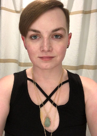 Alex S. Morgan, a femme with short, sleek auburn hair and ivory skin, is smiling softly. They're wearing an elegant black sleeveless top with front cutout detail, and a green semiprecious stone pendant rests in the center of their chest.